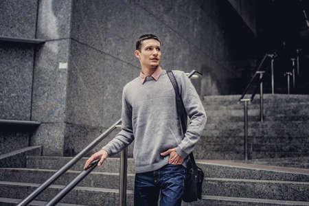 going down: Estudiante en vaqueros y chaqueta gris que va abajo en pasos. Foto de archivo