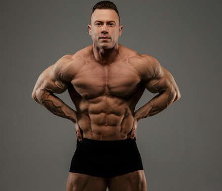 seins nus: Big bodybuilder en culotte noire montrant ses muscles. Isolé sur fond gris.