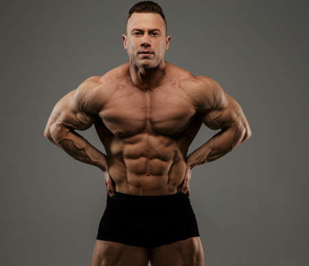 topless: Big bodybuilder in black panties showing his muscles. Isolated on grey background.