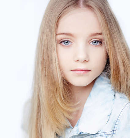 Portrait of teenager girl with long blond hair and blue eyes.
