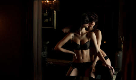 lesbian erotic: Two girls in masks and underwear posing in low light apartments.