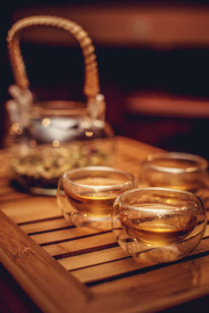 chinese teapot: Chinese teapot with herbal and three glass cups on wooden tray. Stock Photo