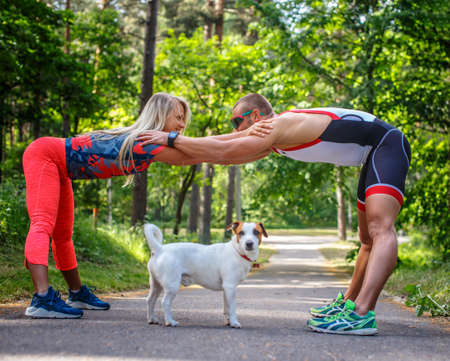 couples outdoors: Man and woman in sportswear doing exercises on the road in forest. Stock Photo
