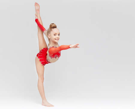 Teenage girl in red dress doing gymnastic exercises on light background.