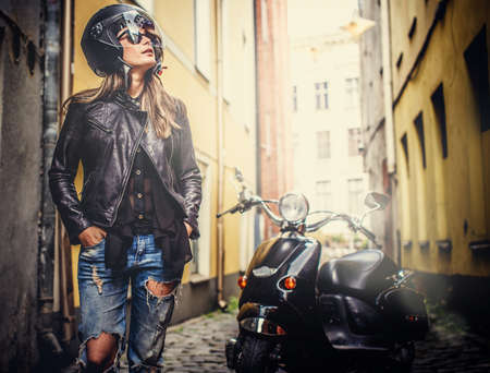 girl bike: Female in blue jeans, leather jacket and motorcycle helmet standing near scooter in old town.