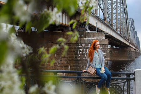 green leafs: Shoot through green leafs of redhead casual young woman. Train bridge on background. Stock Photo