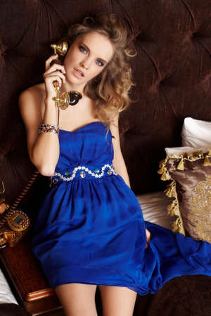 antique phone: Sexy lady in blue dress talking on the antique phone. Stock Photo