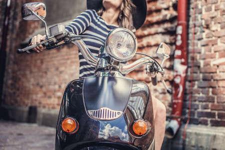 scooter: Atractivo delgado femenino sentado en la vespa en la calle del casco antiguo.
