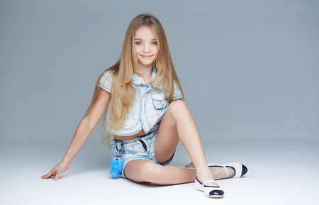 Cute little girl with long blond hair posing on the floor in studio.