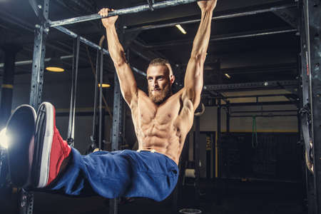 horizontal bar: Shirtless man with deard in blue pants doing exersices on horizontal bar in a gym.