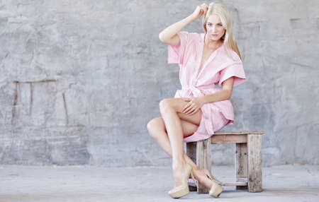 clothing model: Awesome blond woman in pink dress sitting on wooden chair over light grey background. Stock Photo