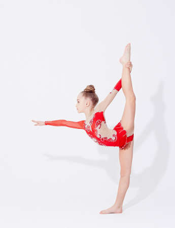 Young flexible girl in red dress doing gymnastic exercises.