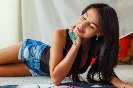 girl lying studio: Sexy woman with long black hair in blue shorts laying on the floor with painting in front of her.