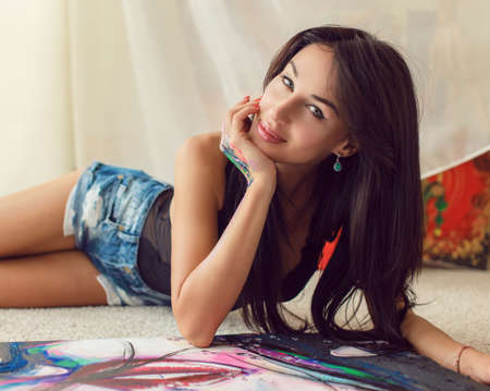 dark hair: Girl with long dark hair in blue shorts sitting on the floor and painting pictures. Stock Photo