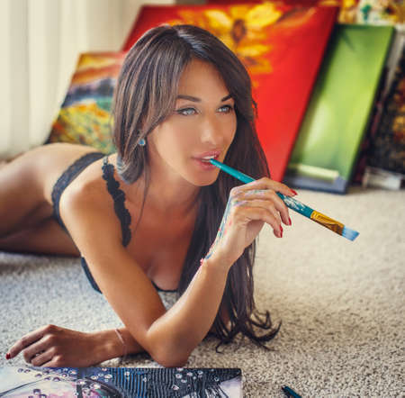 girl lying studio: Portrait of brunette young woman in underwear with brush in her mouth. Colorfull canvas on background.