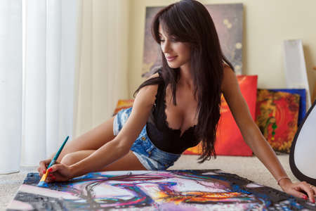 girl lying studio: Sexy young woman with long dark hair laying on the floor with pictures around her.