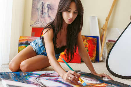 girl lying studio: Girl with long dark hair in blue shorts sitting on the floor and painting pictures. Stock Photo