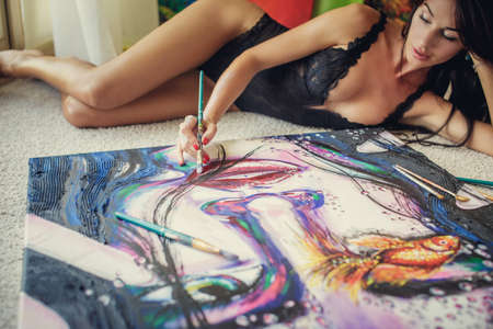 big woman: Sexy woman lying on the floor and painting big pattern.