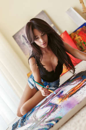 girl lying studio: Sexy brunette woman in underwear sitting on the floor with colorful picture in front of her.