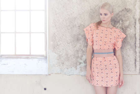 Portrait of blond female in pink dress over grey wall.