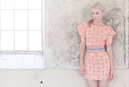 회색 벽 위에 핑크 드레스에 금발 여성의 초상화입니다.