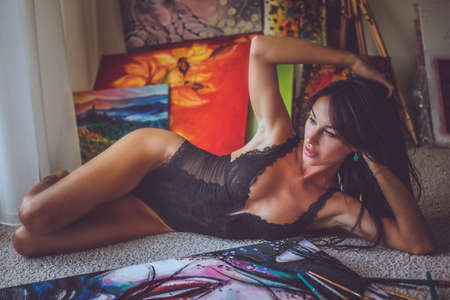 sexy brunette woman: Sexy brunette woman in underwear lying on the floor with paintings on background. Stock Photo