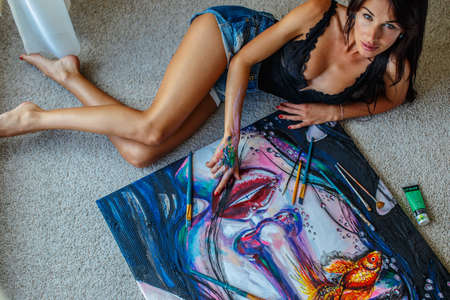 girl lying studio: Sexy woman lying on the floor and painting big pattern.