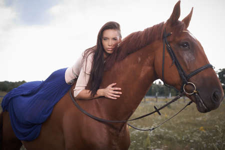 cowgirl hat: Fashion girl in long blue scirt lying on brown horse over white sky. Stock Photo