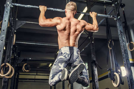 barra: Hombre sin camisa tirando hacia arriba de la barra horizontal en un gimnasio.