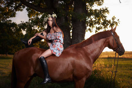 Fashion brunette woman in colorful dress and long leather boots sitting on brown horse over nature scene on background.