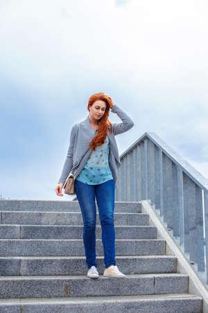 down the stairs: Redhead ocasional chica caminando por las escaleras.