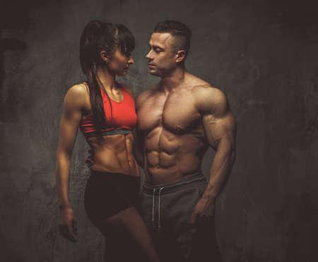 Beautiful bodybuilders couple posing over grey background.
