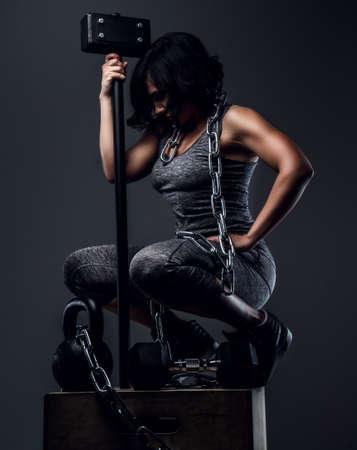 ropa deportiva: Mujer con el pelo negro y corto en ropa deportiva gris sentado en caja de madera y la celebración de grandes hummer.