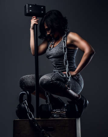 sportswear: Woman with short black hair in grey sportswear sitting on wooden box and holding big hummer.