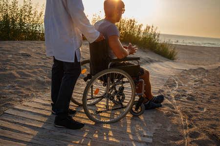 Jonge man in rolstoel en zijn arts ontspannen op de weg naar het strand.