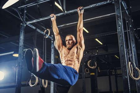 musculoso: hombre sin camisa muscular que hace tirando hacia arriba de la barra horizontal.