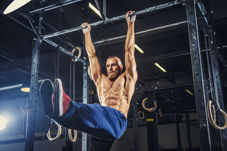 Muscular shirtless man doing pulling up on horizontal bar. 免版税图像