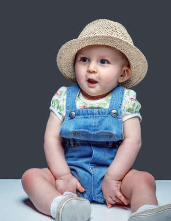 baby girl: Cute little child in jeans costume and summer hat.