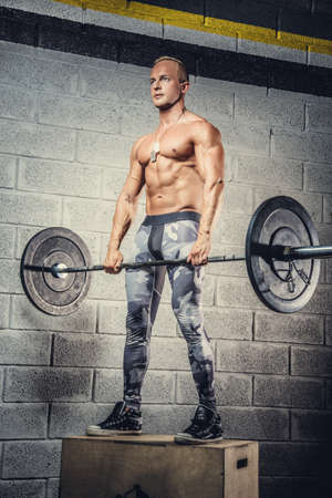 sixpacks: Full body portrait of sporty man  in military pants, with weights bar in hands over grey wall.