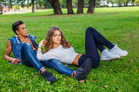 family and friends: Casual male and female lying on grass field in a park.