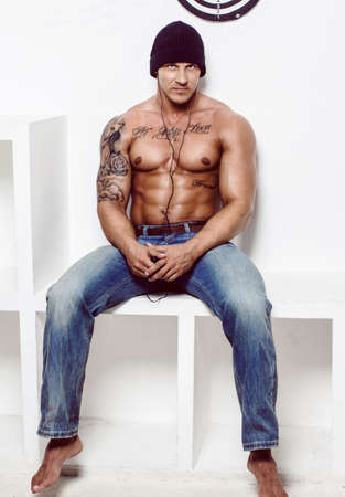 Shirtless muscular man with tatooes in blue jeans sitting on square podium over white wall.