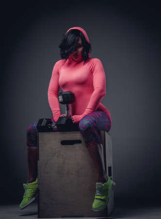 sportswear: Awesome brunette woman in colorful sportswear sitting on wooden box and holding dumbbell. Stock Photo