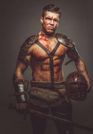pezones: gladiador con sangre en la espada de retención armadura. Aislado en el fondo gris.