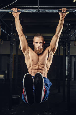 pull up: Muscular brutal man with beard doing pull up on horizontal bar in a gym. Stock Photo