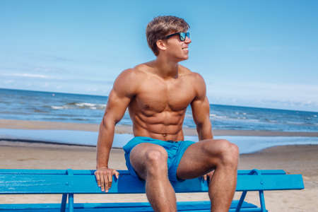 Awesome muscular young guy in blue swim shorts sitting on bench over blue sky and sea.