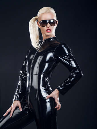 fetishism: Sexy blond female in sunglasses and in latex black costume isolated on dark background.