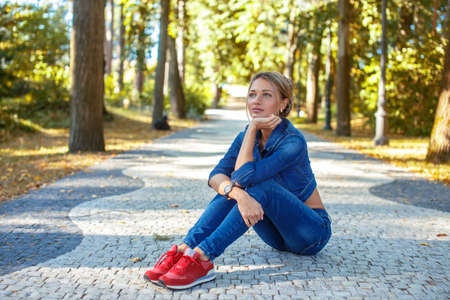 red shoes: Slim blond female in jeans costume and red shoes sitting on the road in a park.