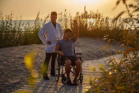 silla de ruedas: Hombre joven en silla de ruedas y su médico de relax en la playa durante la puesta del sol.