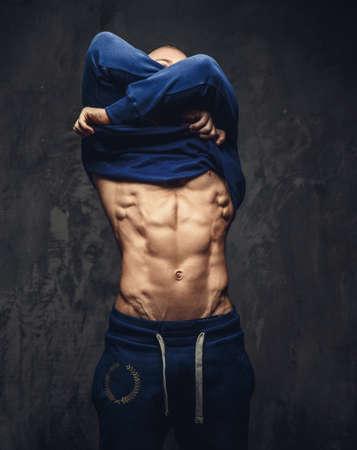 fitness hombres: Individuo muscular en ropa deportiva desvestirse. Aislado en el fondo gris. Foto de archivo