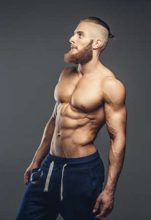 sixpacks: Shirtless muscular guy with beard posing in studio over grey background.
